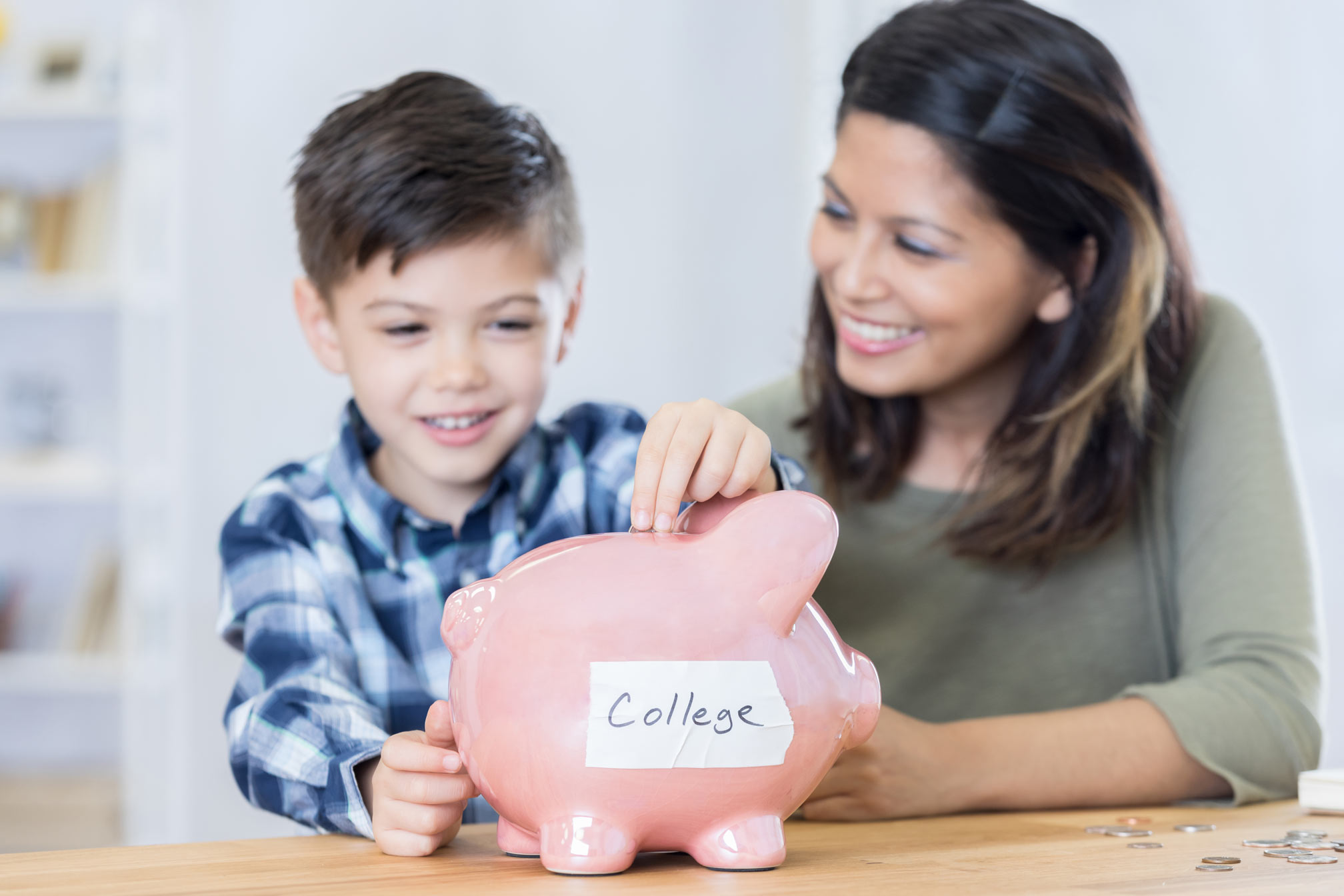 Mother teaching son the value of saving for college